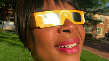 Smiling woman with eclipse glasses